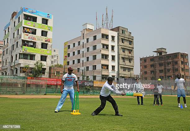 Johnson Charles of the West Indies wicketkeeps and Darren Sammy captain of the West Indies looks on as they play a game of cricket with children...
