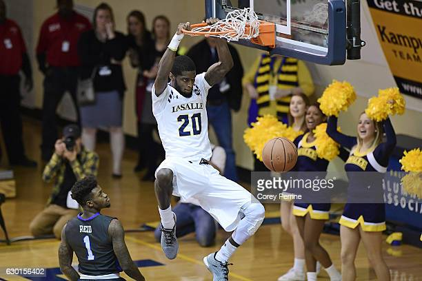 J Johnson of the La Salle Explorers scores the final two points of the game on a dunk with about 8 seconds remaining as Reggie Reid of the Florida...