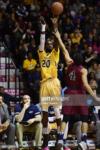 J Johnson of the La Salle Explorers shoots over Darnell Foreman of the Pennsylvania Quakers during the second half at Tom Gola Arena on January 25...