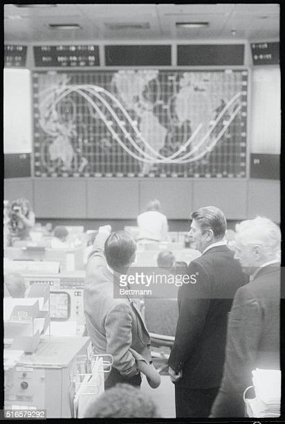 Johnson Space Center Director Christopher Kraft Jr points to the orbit tracking map in Mission Control telling President Reagan the current location...
