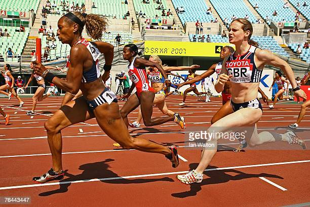 Joice Maduaka of Great Britain receives the baton from Emily Freeman of Great Britain while they compete during the Women's 4 x 100m Relay Heats on...