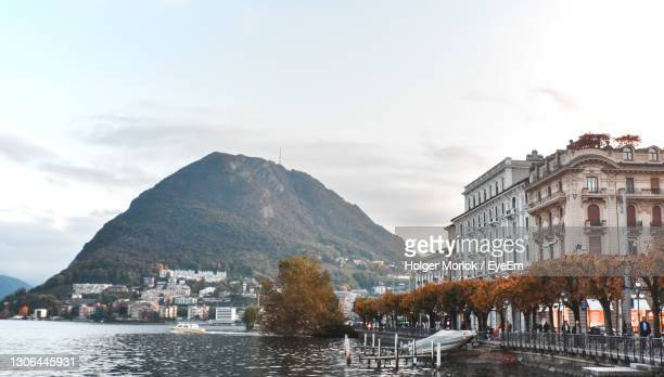 join this wonderful in lugano during the late afternoon. buildings by mountains against sky in city. - スイス ルガーノ ストックフォトと画像