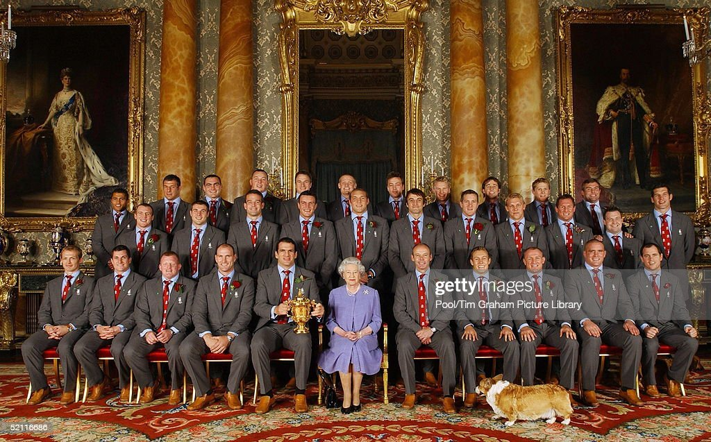 Joined By One Of Her Pet Corgis The Queen Poses With The England Rugby Squad At Buckingham Palace To Celebrate The Rugby World Cup Win. Front Row (l-r): Matt Dawson, Paul Grayson, Dorian West, Lawrence Dallaglio, Martin Johnson, Her Majesty, Clive Woodward, Jonny Wilkinson, Neil Back, Phil Vickery And Kyran Bracken. Back Row (l-r): Jason Robinson, Julian White, Trevor Woodman, Steve Thompson, Mike Catt, Iain Balshaw, Dan Luger, Stuart Abbott, Andy Gomarsall, Josh Lewsey And Jason Leonard. Centre Row ( L-r): Mike Tindall, Ben Cohen, Joe Worsley, Martin Corry, Ben Kay, Danny Grewcock, Will Greenwood, Lewis Moody, Richard Hill, Mark Regan And Simon Shaw.