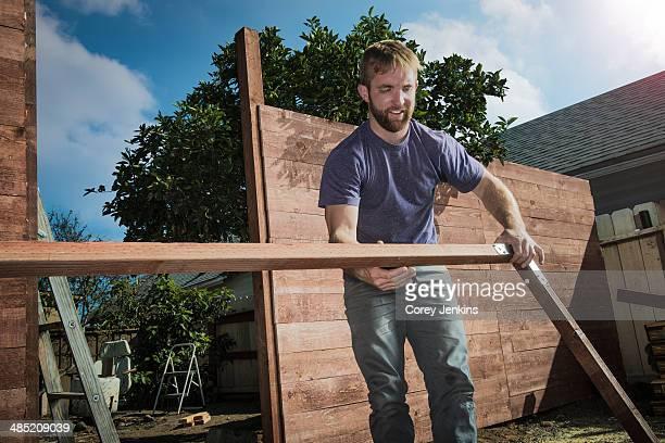 Joiner in backyard lifting wood framework