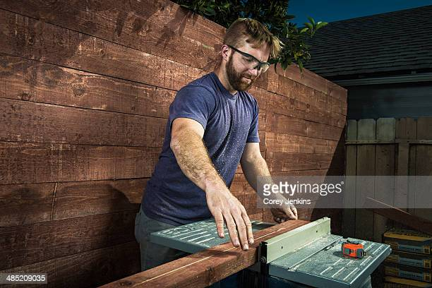 Joiner in backyard lining up planks of wood on workbench
