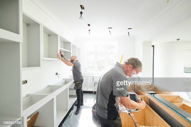 joinery team fitting a kitchen - craftsman stock photos and pictures