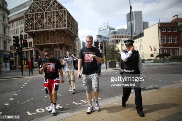 Joint EDL leaders Tommy Robinson and Kevin Carroll talk to a police officer as they enter Tower Hamlets on June 29 2013 in London England The leaders...