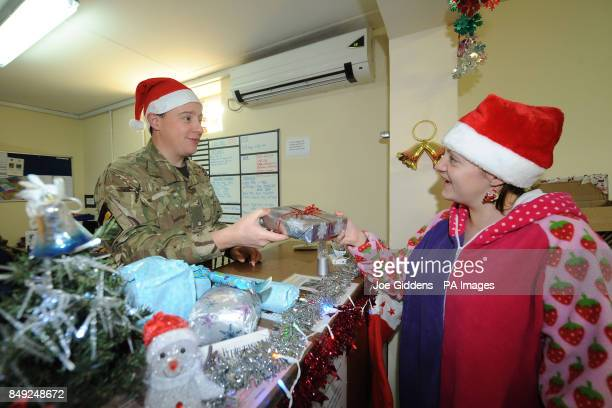 Joint Force Medical Group's Major Colin Wall from Wiltshire hands a Christmas present to Lance Corporal Hannah Gibson from Newcastle at main...