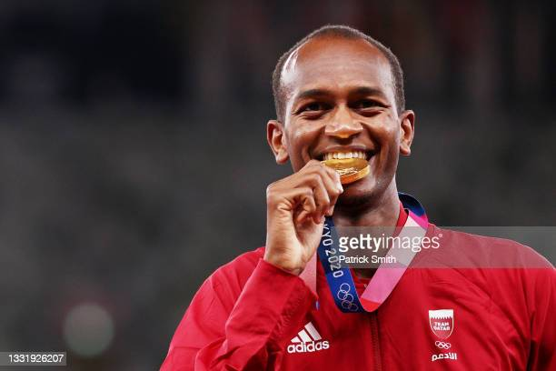 Joint gold medalist Mutaz Essa Barshim of Team Qatar bites his medal on the podium during the medal ceremony for the Men's High Jump on day ten of...