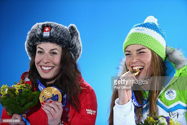 Joint gold medalists Dominique Gisin of Switzerland and Tina Maze of Slovenia celebrate during the medal ceremony for the for the Alpine Skiing...