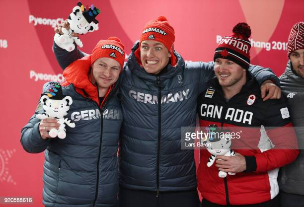 Joint gold medalists Francesco Friedrich and Thorsten Margis of Germany and Justin Kripps of Canada celebrate during the victory ceremony after the...