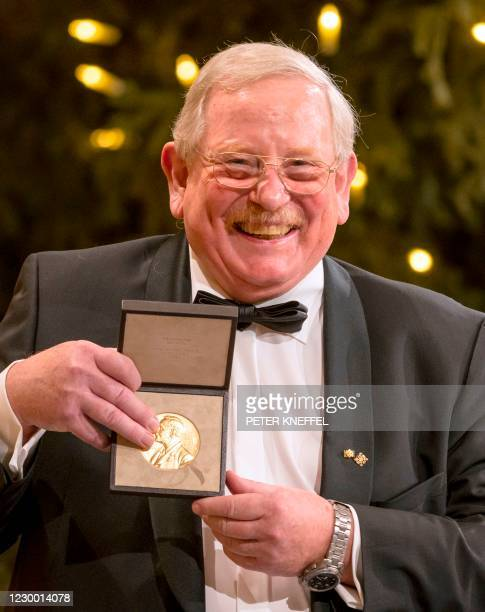 Joint Nobel Physics laureate Reinhard Genzel poses with his medal received at Bavarian State Chancellery in Munich, southern on December 8, 2020. -...