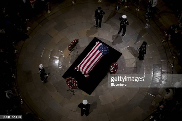 Joint services military honor guards stand next to the flagdraped casket of former US President George HW Bush on the Lincoln catafalque during a...