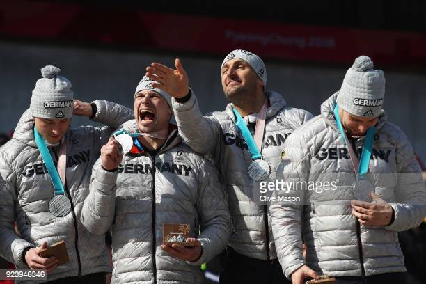 Joint silver medalists Nico Walther Kevin Kuske Alexander Roediger and Eric Franke of Germany celebrate on the podium during the medal ceremony after...