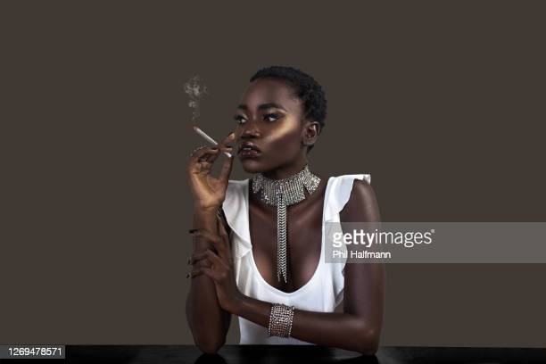 joint smoking black lady in silver jewelry - black nail polish stock pictures, royalty-free photos & images