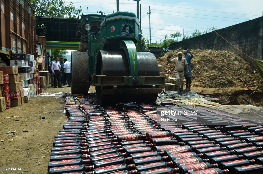 Joint team of Excise and Assam Police official destructed seized liquor under the supervision of team of officials and under the aegis of Assam Excise and police in presence of Excise Minister of Assam, Parimal Suklabaidya and Magistrate at Garchuk in Guwahati, Assam, India on Friday, August 10, 2018.