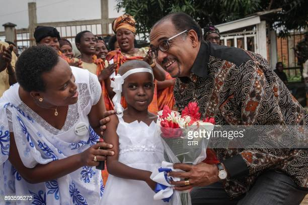 Joint United Nations Programme on HIV/AIDS Executive director and UN Deputy General Secretary Michel Sidibe receives a bouquet of flowers from a girl...