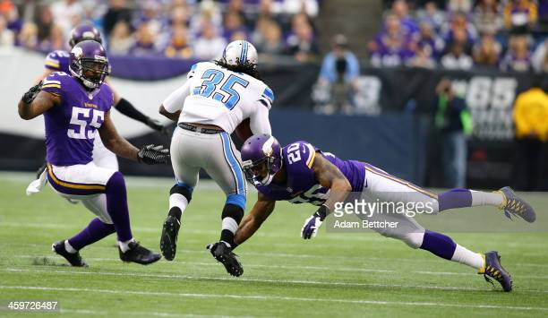 Joique Bell of the Detroit Lions carries the ball for a gain while Marvin Mitchell and Chris Cook of the Minnesota Vikings make the tackle on...