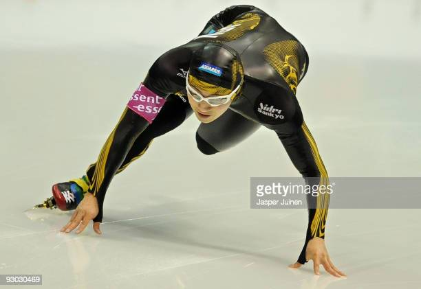 Joji Kato of Japan uses his hands to keep his balance as he competes in the 500m race during the Essent ISU speed skating World Cup at the Thialf...