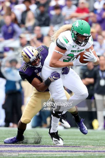 JoJo McIntosh of the Washington Huskies tackles Luke Fiedler of the North Dakota Fighting Sioux in the second quarter during their game at Husky...
