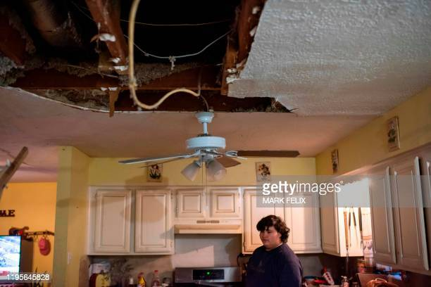 Jojo Munguia looks at where his family's kitchen ceiling fell after an explosion at a northwest Houston, Texas, manufacturing business, on January...