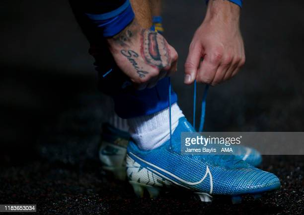 Joker tattoo on the hand of Jason Cummings of Shrewsbury Town as he ties his boot laces before the FA Cup First Round Replay match between Bradford...