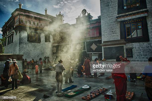 CONTENT] Jokhang Monastery in Lhasa Tibetan Buddhist worshippers prostrate themselves around the entrance in the morning light as part of their daily...