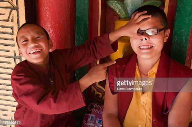 Joking young Tibetan-Sherpa monks having fun at a monastery at Bodhnath in Kathmandu, Nepal