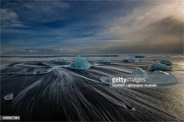 Jokulsarlon Beach in winter, just after a huge storm hit the coastline. Ice bergs from the nearby lagoon have been swept up onto the coastline and surge in and out with the tide.