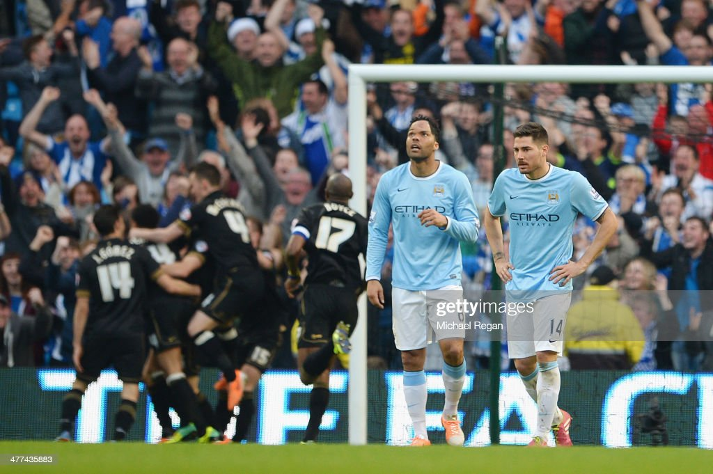 Joleon Lescott and Javi Garcia look dejected as Wigan celebrate the second goal during the FA Cup Quarter-Final match between Manchester City and Wigan Athletic at the Etihad Stadium on March 9, 2014 in Manchester, England.