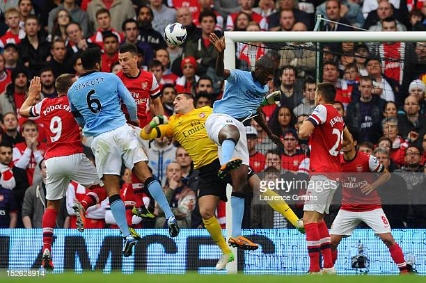 Joleon Lescott of Manchester City beats Vito Mannone of Arsenal to the ball to score the first goal during the Barclays Premier League match between...