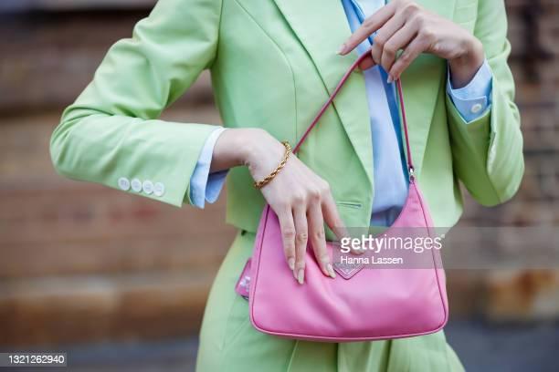 Jolie Nguyen, bag detail, wearing Nudie Eye green cropped suit, Prada pink bag and Bottega Veneta shoes at Afterpay Australian Fashion Week 2021 on...