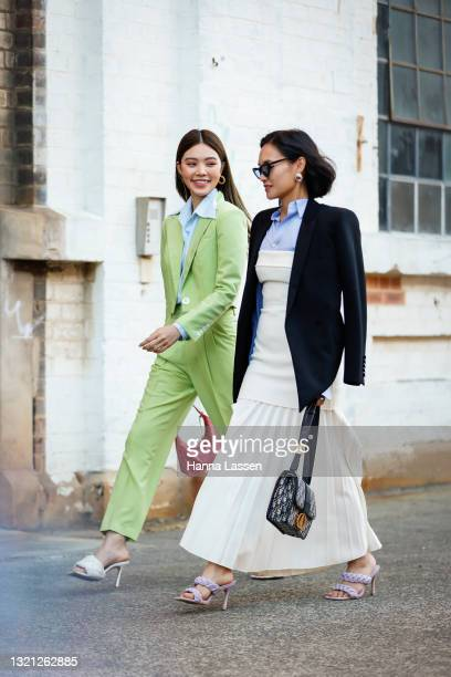 Jolie Nguyen wearing Nudie Eye green cropped suit, Prada pink bag and Bottega Veneta shoes and Christine Ai wearing Dion Lee dress, Tom Ford shirt,...