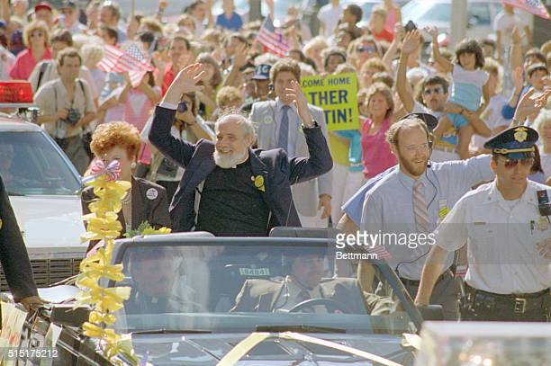 Former hostage Reverend Lawrence Jenco acknowledges cheers as he rides in parade through his hometown Left is Mrs George O'Brien widow of Illinois...
