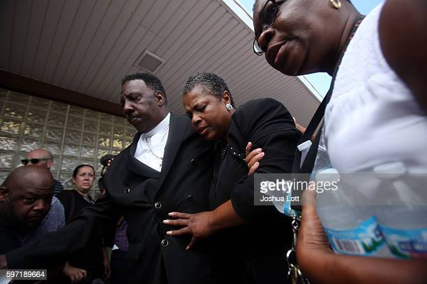 Jolinda Wade center the aunt of Nykea Aldridge and mother of basketball player Dwyane Wade is lead away after being overcome by emotions during a...