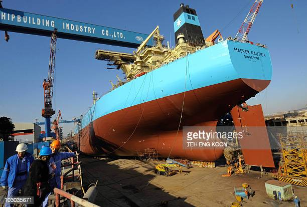 STORY CHINAECONOMYINDUSTRYSHIPPING BY Joëlle GARRUS Visitors stand near an underconstruction 300000tonne oil tanker at a shipyard in northeast...