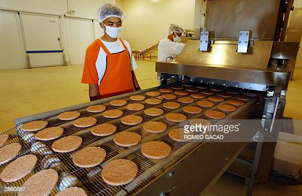 Jollibee plant personnel watch over the fresh hamburger patties produced at the new 15 billion peso Jollibee commissary in Canlubang town south of...