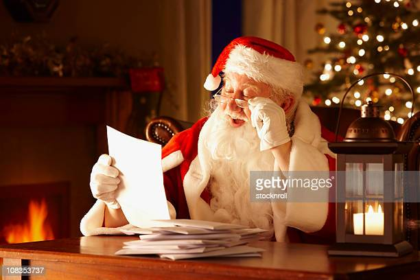 jolly father christmas reading letters from children - bericht stockfoto's en -beelden