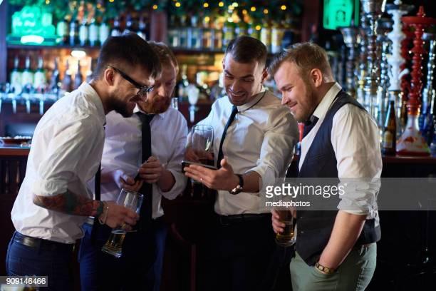 Jolly men using gadget in bar