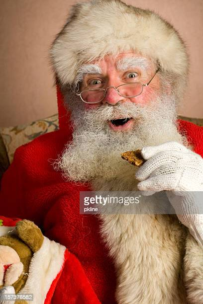 jolly santa has a cookie - santa face stock pictures, royalty-free photos & images