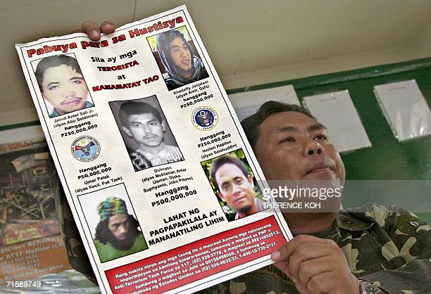 Major Mabini Abduhadi shows a poster of the wanted AlQueda linked Abu Sayyaf leaders Camp Baustista in Jolo 05 July 2006 The Philippines military...