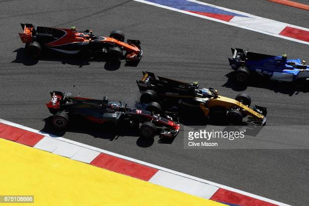Jolyon Palmer of Great Britain driving the Renault Sport Formula One Team Renault RS17 and Romain Grosjean of France driving the Haas F1 Team...