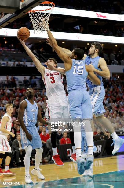 Jon Axel Gudmundsson of the Davidson Wildcats drives to the basket against teammates Garrison Brooks and Luke Maye of the North Carolina Tar Heels...