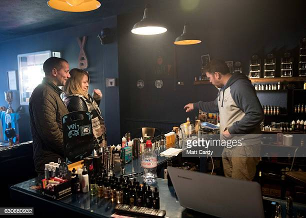 Jon Bartlett who runs the Vapour Place a vaping shop in Bedminster serve a customer on December 30 2016 in Bristol England Recent figures released by...