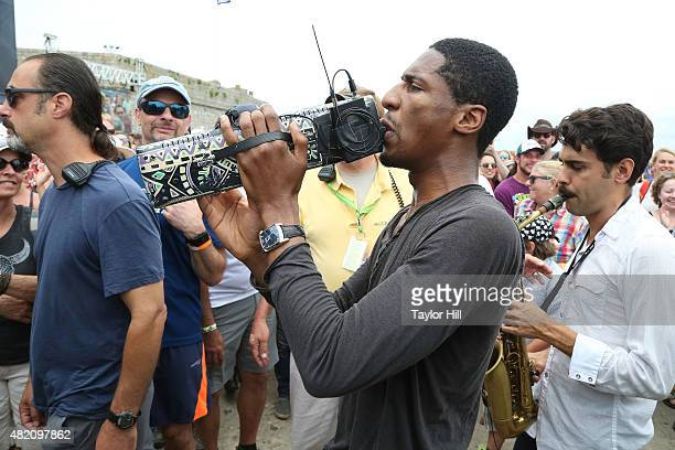 Jon Batiste the new bandleader for Late Night with Stephen Colbert leads a second line through the crowd during the 2015 Newport Folk Festival at...