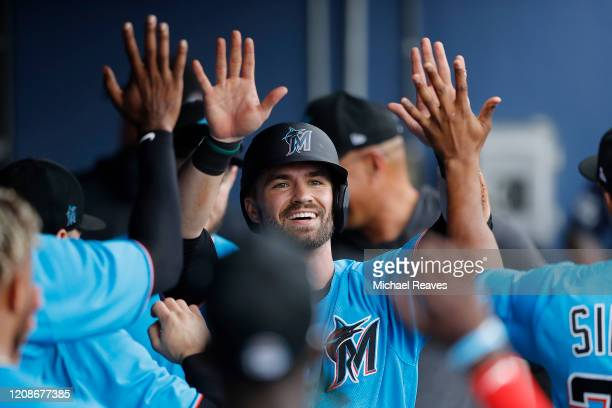 Jon Berti of the Miami Marlins celebrates with teammates after scoring a run against the Houston Astros in the fifth inning of a Grapefruit League...