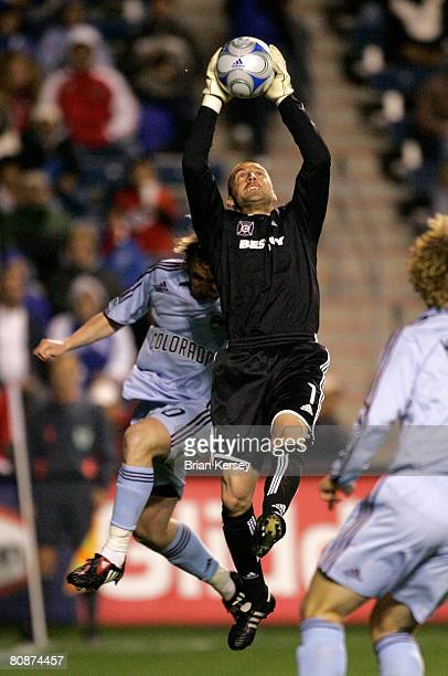 Jon Busch of the Chicago Fire makes a save as Tom McManus of the Colorado Rapids goes for the ball during the second half at Toyota Park on April 26...