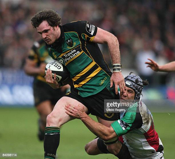 Jon Clarke of Northampton is tackled by De Wet Barry during the Guinness Premiership match between Northampton Saints and Harlequins at Franklin's...