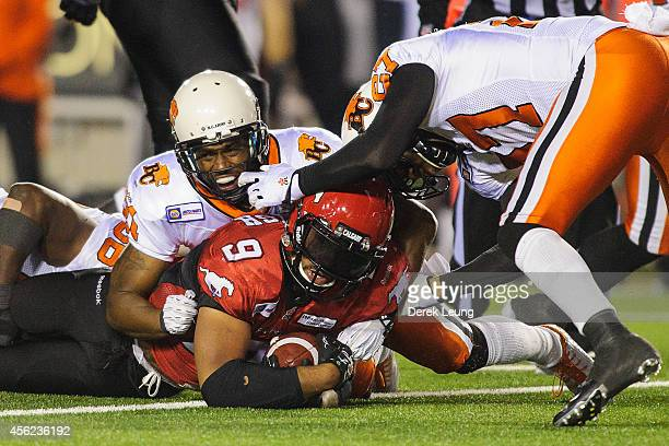 Jon Cornish of the Calgary Stampeders gets stopped by Solomon Elimimian Ryan Phillips and JR LaRose of the BC Lions during a CFL game at McMahon...