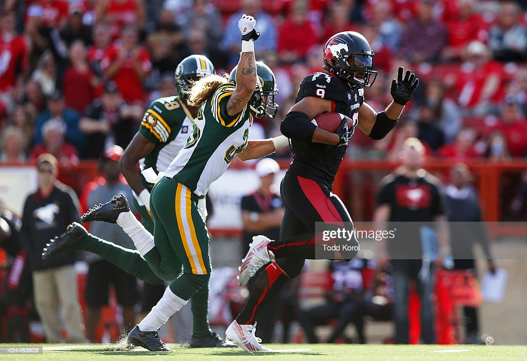 Jon Cornish #9 of the Calgary Stampeders runs past Aaron Grymes #36 and Patrick Watkins #9 of the Edmonton Eskimos in the second half of their CFL football game September 1, 2014 at McMahon Stadium in Calgary, Alberta, Canada.